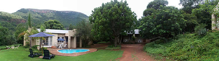 Photo of the pool area, self-catering suites and cottage on the right